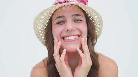 olhos castanhos : Happy woman wearing a hat while hiding her face against a white background