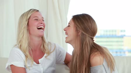 дружба : Happy young women talking to each other in a bright living room Стоковые видеозаписи