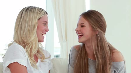 beszélő : Laughing friends talking to each other in the living room