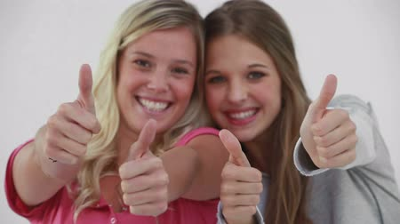 жест : Smiling young women placing their thumbs up against a grey background Стоковые видеозаписи