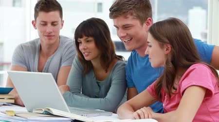 друзья : Smiling students using a laptop together in a bright room