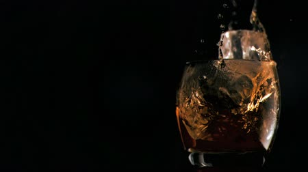 whisky : Ice cubes falling in super slow motion into a glass with liquor