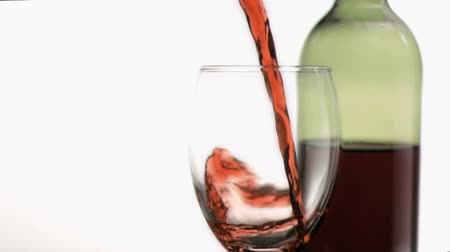 beyaz şarap : Red wine poured in super slow motion into a glass against a white background