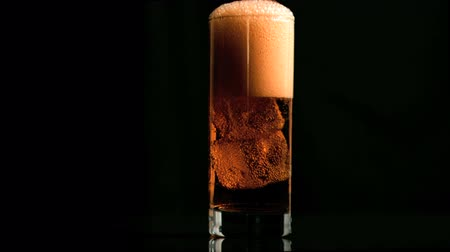 pezseg : Fizzy drink with ice in super slow motion against black background