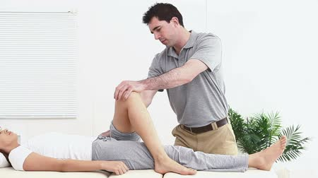 fizjoterapeuta : Physiotherapist stretching the leg of his patient in a room Wideo