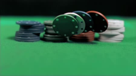 покер : Gambling chips falling in super slow motion on green table against black background