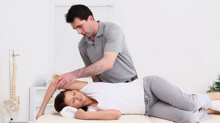 terapeuta : Physiotherapist massaging the back of a patient in a room