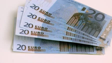 loans : Twenty euros banknotes spread in super slow motion against white background