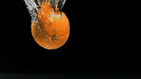 citrusové plody : Orange diving in super slow motion in water against black background