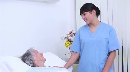 talk : Nurse talking to a senior woman in her bed at hospital