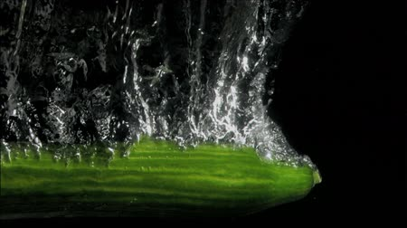 pepino : Tasty cucumber in super slow motion falling in the water against a black background