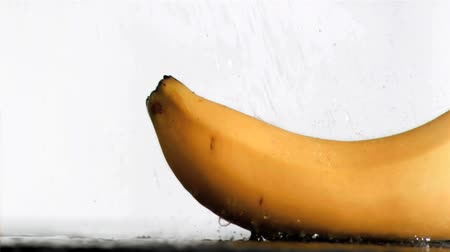 muz : Delicious banana in super slow motion receiving water against a white background Stok Video