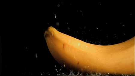 banany : Delicious banana in super slow motion being soaked against a black background