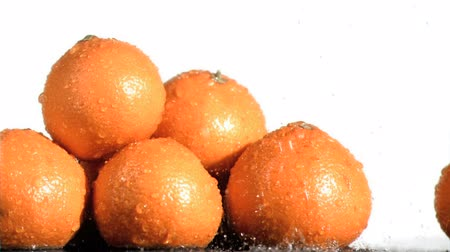 laranjas : Tasty oranges in super slow motion being soaked against a white background