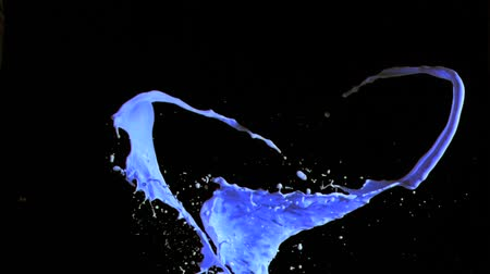 boyalar : Blue sprays of paint in super slow motion mixing against a black background Stok Video