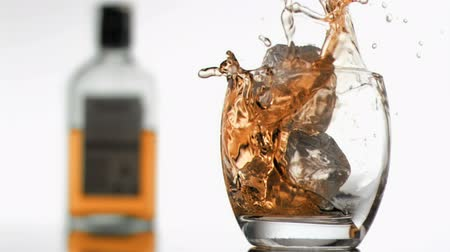 viski : Ice cubes in super slow motion falling in a glass of whiskey against a white background