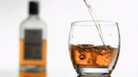 viski : Bourbon in super slow motion filling a glass against a white background
