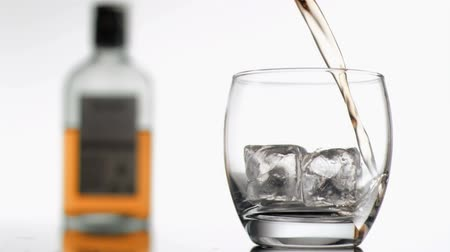 viski : Whiskey in super slow motion filling a tumbler against a white background Stok Video