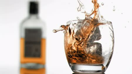 viski : Whiskey in super slow motion overflowing against a white background Stok Video