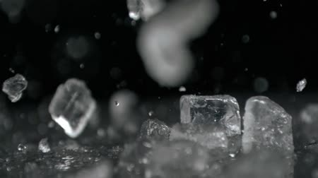 gelado : Ice falling in super slow motion against black surface