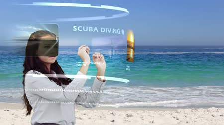 interaktif : Brunette woman looking at holiday activities on interactive media library on beach