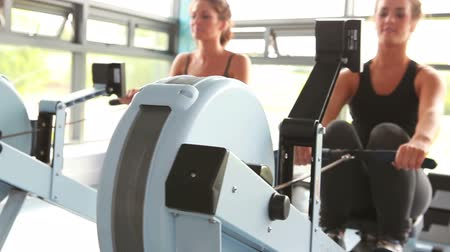 evezés : Two women drawing on row machine in gym