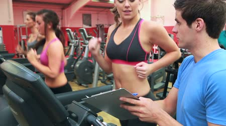 tornaterem : Trainer talking to woman on treadmill in gym