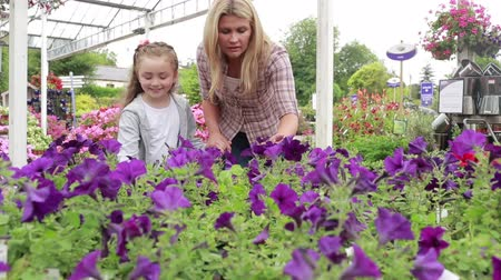 цветочный : Mother and child standing at the garden centre looking at flowers