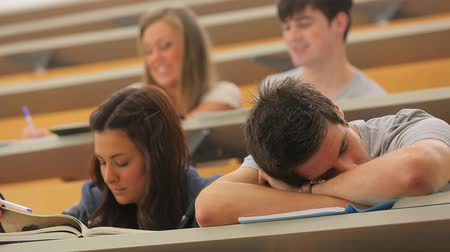 wykład : Student sleeping at the lecture hall leaning on table
