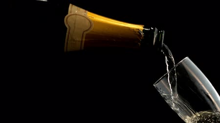 бутылки : Bottle filling champagne flute against black background
