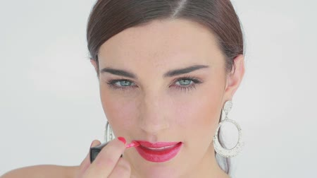 deslumbrante : Woman applying pink lip gloss while smiling