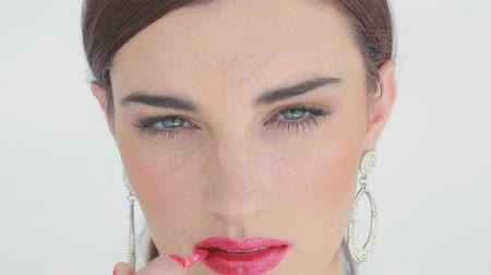 makijaż : Woman colouring her lips with pink lip gloss