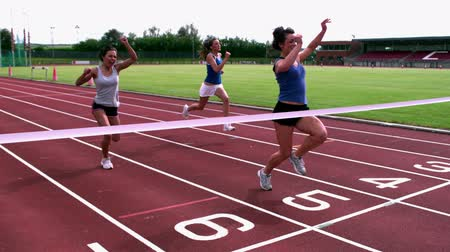 pista de corridas : Athletes crossing the finish line on the track Stock Footage