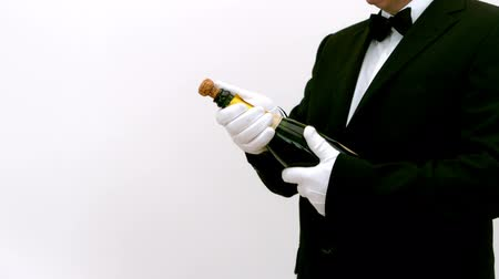szampan : Man opening a bottle of champagne against a white background