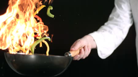 culinária : Chef tossing stir fry in flaming wok in slow motion