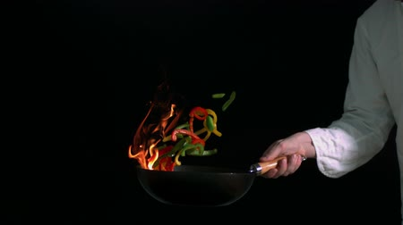 chef cooking : Peppers burning in a pan with little flame in slow motion