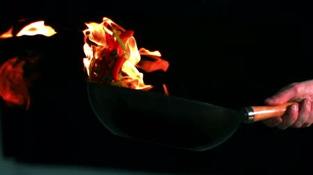 frigideira : Chef tossing flaming pan of peppers in slow motion