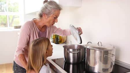 cooking pots : Girl happily cooking with her grandmother in kitchen