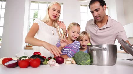 cooking pots : Posing family putting vegetables in a pot together