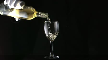 porce : Gloved hand pouring white wine into glass in slow motion