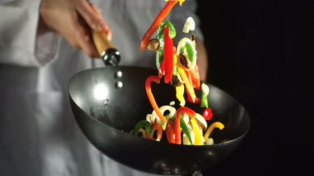 culinária : Chef making vegetable stir fry in wok in slow motion