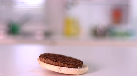 hambúrguer : Burger falling on bun in kitchen in slow motion Vídeos