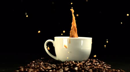 kahve çekirdeği : Sugar cube falling in coffee cup and splashing in slow motion Stok Video