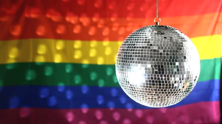 orgullo gay : Bola de disco giratorio contra la bandera del orgullo gay con luz refelction Archivo de Video
