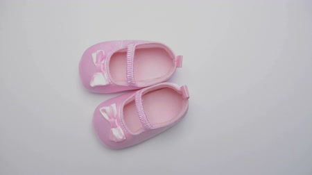 booties : Pink baby booties on revolving white surface Stock Footage