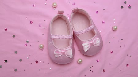 booties : Pink baby booties on pink blanket with pearls revolving video