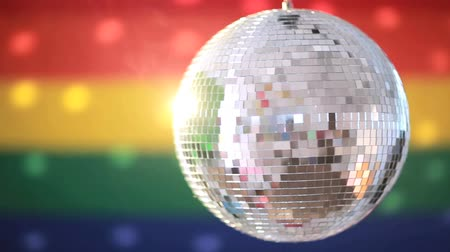 homoszexuális : Shiny disco ball revolving against rainbow flag background