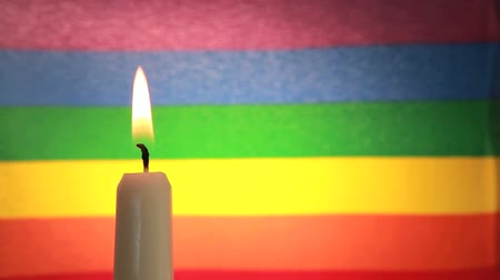 гей : Candle lighting against rainbow flag and then blown out