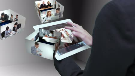 munkacsoport : Businesswoman using tablet to view montage of business people at work in holographic form