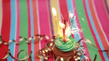 dilek : Birthday cupcake with sparkler and candle on rainbow background